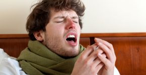 25324361 - man with sinus infection sneezing in bed