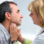 30111819 - female doctor touching the throat of a patient in the office